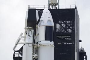 2 astronauts climb aboard SpaceX rocket for historic flight