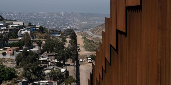 Mexican protesters hold 'stay at home' signs on the border with the US over fear of the coronavirus outbreak